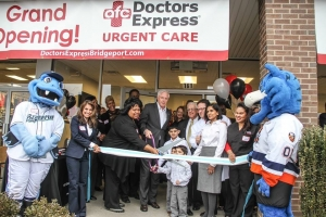 Bridgeport Mayor Bill Finch (center) gets assistance from Deborah Caviness, Director of the City of Bridgeport's Small, Minority Business Resource Office and Doctors Express Bridgeport Medical Director, Dr. Steven Heffer and his family for the Official Ribbon Cutting Grand Opening of Doctors Express Bridgeport (161 Boston Ave.).  (from left) Bridgeport Bluefish, Doctors Express Bridgeport Marketing Director Yvonne Lederer, Deborah Caviness, Mayor Finch, Bridgeport Regional Business Council President Paul Timpanelli, Dr. Heffer and his wife, Dr. Heena Sultan, Doctors Express Bridgeport LPN Desiree Velazquez and Storm the Bridgeport Sound Tiger.